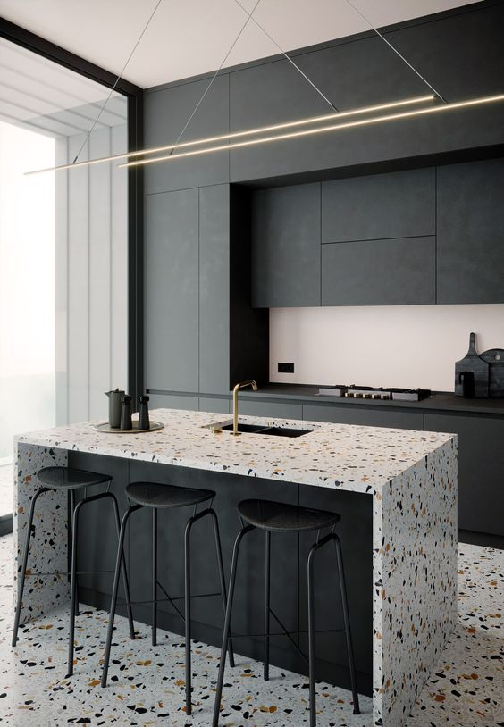 a minimalist black kitchen with sleek no handles cabinets, a gorgeous kitchen island with a terrazzo waterfall countertop and a matching floor