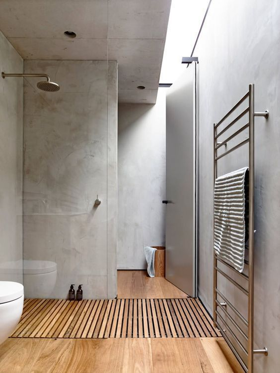 a minimalist concrete bathroom with a wooden floor looks much cozier and more welcoming is very cool