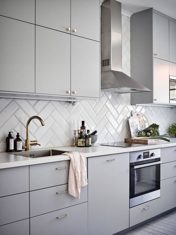 a minimalist dove grey kitchen with a glossy white herringbone backsplash and brass touches is a stylish and chic idea