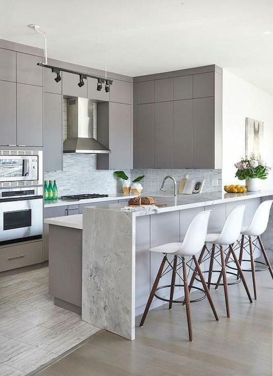 a minimalist grey kitchen with a matching kitchen island and an additional raised waterfall countertop of white stone for chic