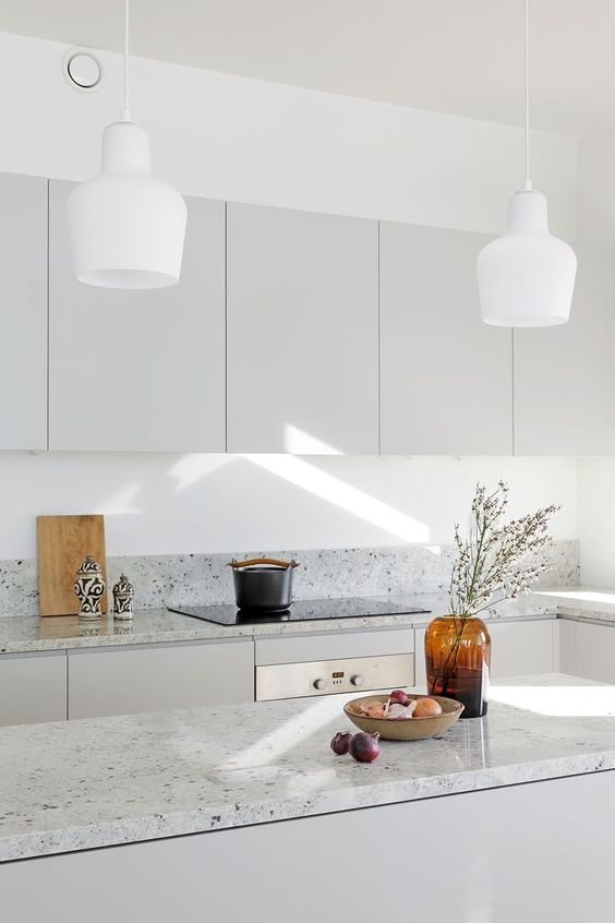 a minimalist grey kitchen with grey terrazzo countertops and white pendant lamps is a chic and welcoming space