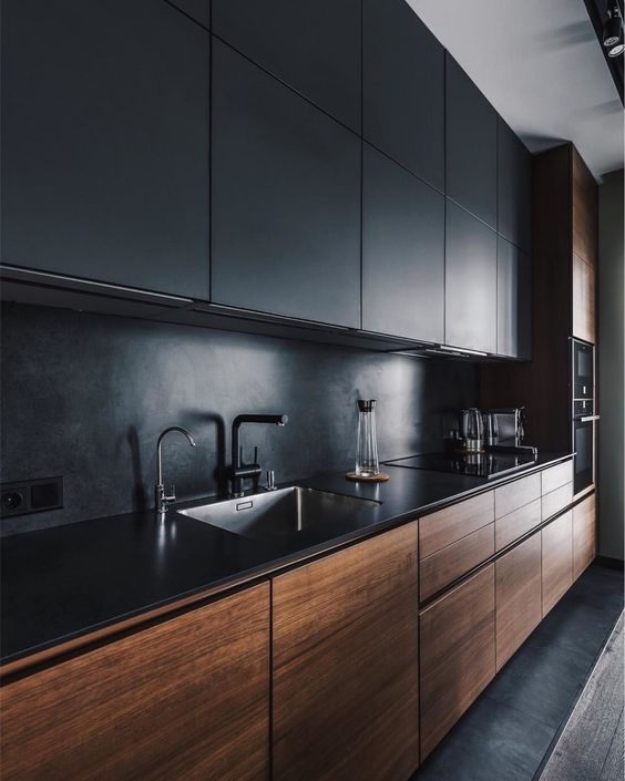 a minimalist kitchen with black and stained sleek cabinetry, a black stone backsplash and countertops plus black fixtures