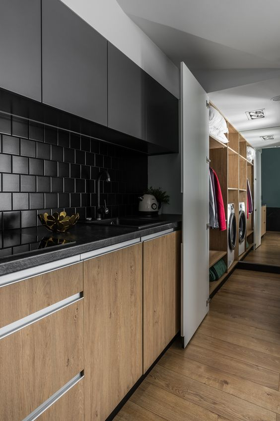 a minimalist kitchen with stained and black cabients, a matte black square tile backsplash and black countertops looks chic