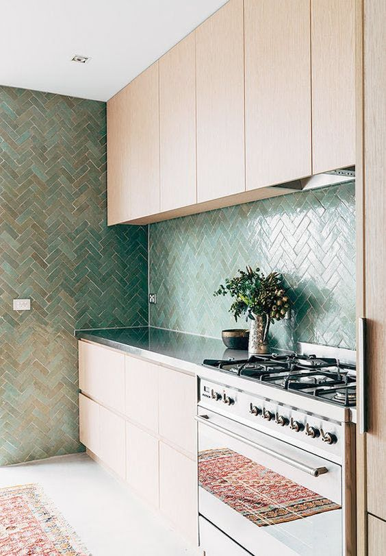 a minimalist light stained kitchen with a stainless steel countertop and a herringbone backsplash and a wall for more interest