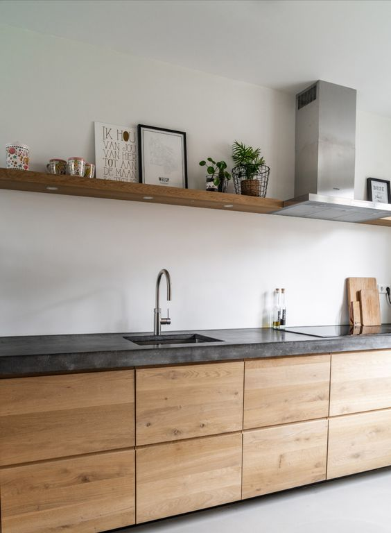 a minimalist light stained kitchen with a thick concrete countertops, a wooden shelf and stainless steel appliances