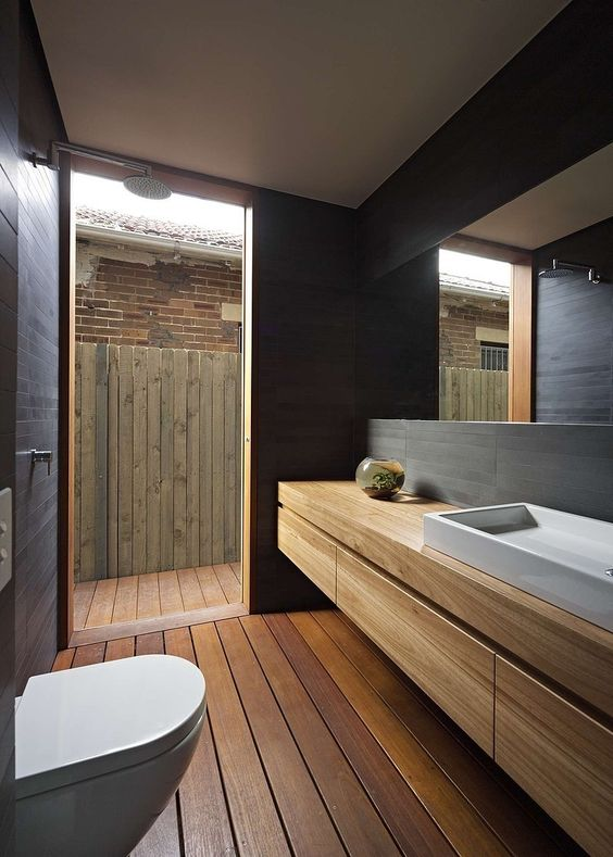 a minimalist outdoor-indoor bathroom clad with wood and with a floating wooden vanity plus dark skinny tiles