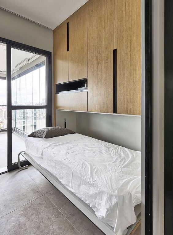a minimalist space with a large closed storage unit that contains a small Murphy bed and saves space
