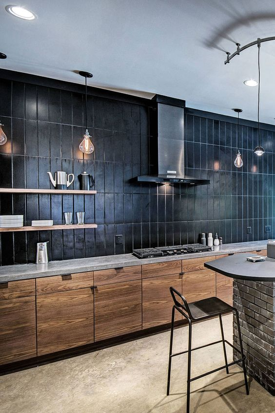 a minimalist stained kitchen with a grey quartz countertop plus a black large scake stacked tile backsplash that takes a whole wall