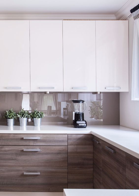 a minimalist two tone kitchen with stained and white cabinets, a brown glass backsplash and white quartz countertops and modern fixtures