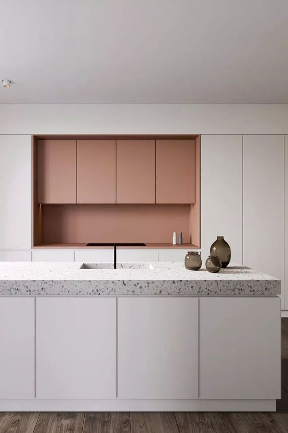 a minimalist white and coral kitchen with no handles and a grey terrazzo countertop that adds pattern to the space
