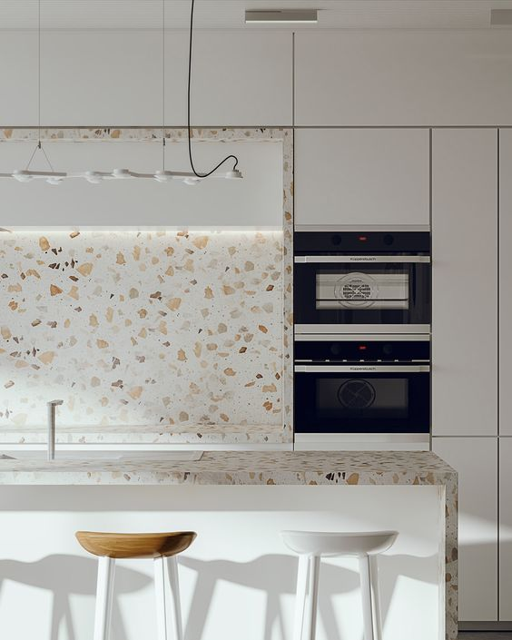a minimalist white kitchen with cool white terrazzo countertops and a backsplash plus a pendant lamp is amazing