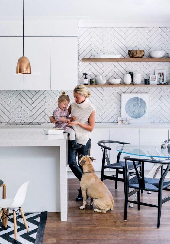 a minimalist white kitchen with sleek cabinetry, white stone countertops, a white herringbone backsplash and copper touches