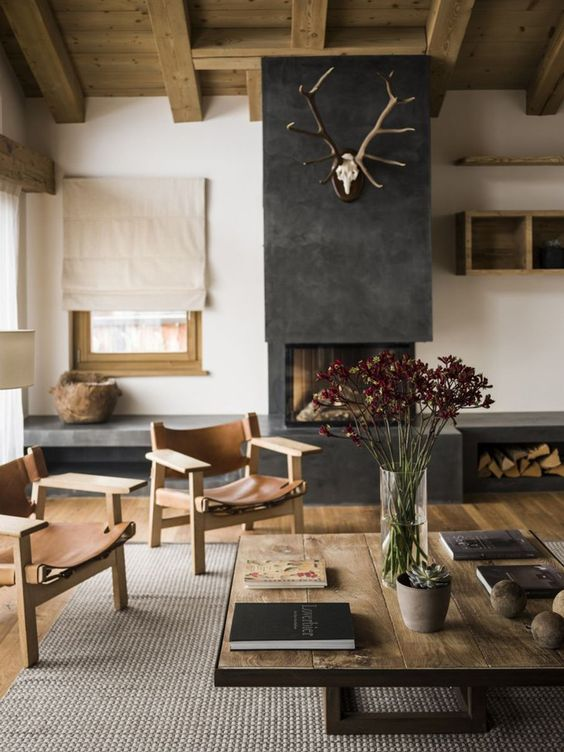 a modern chalet living room with a wooden ceiling, leather chairs and a wooden table plus a concrete fireplace with a storage compartment