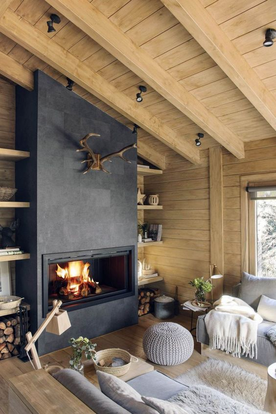 a modern chalet living room with wooden walls and a ceiling, a concrete fireplace, firewood storage, grey sofas