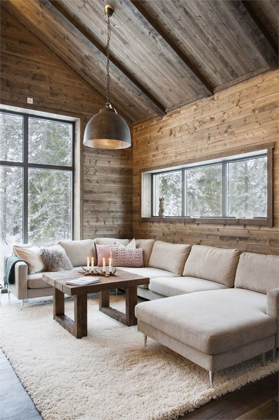 a modern chalet living room with wooden walls and a ceiling, a neutral sectional, a metal pendant lamp