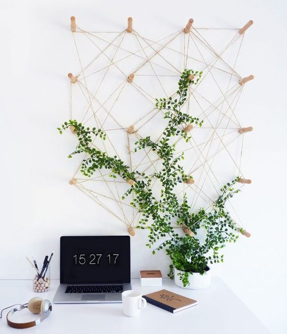 a modern home office accented with a climbing plant covering a yarn piece that can be used for memos, too