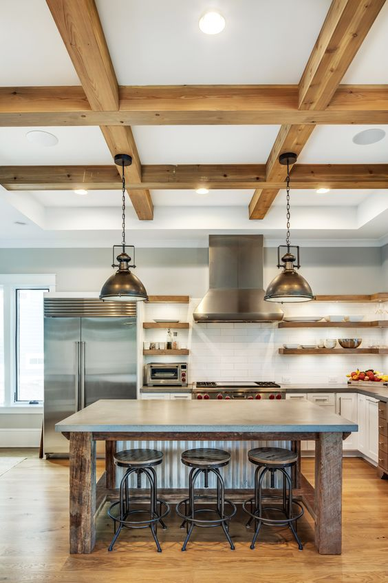 a modern industrial kitchen with white cabinets and a rough wood kitchen island, concrete coutnertops, wooden beams and pendant lamps