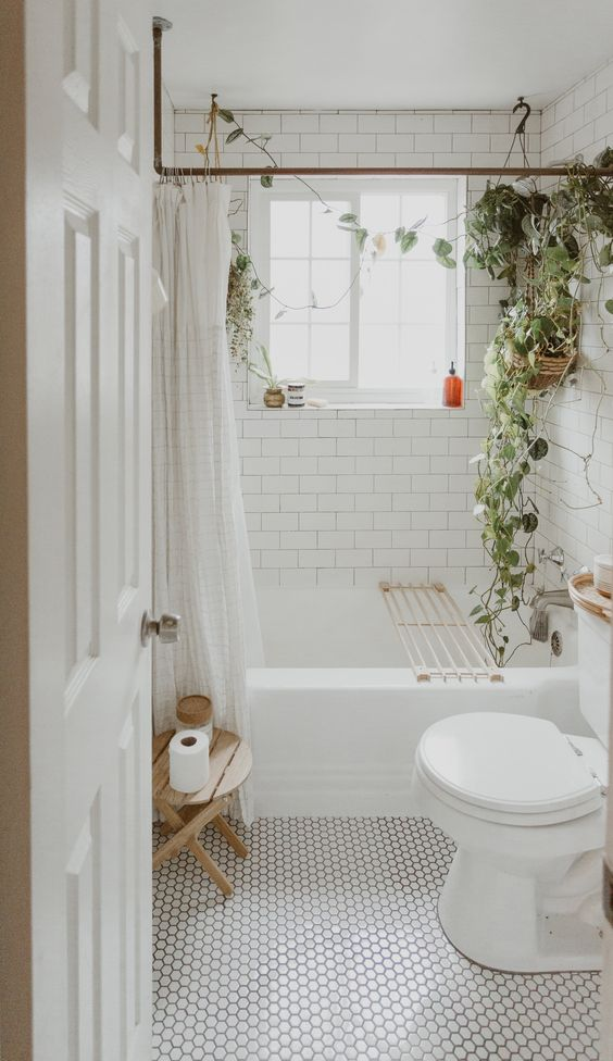 a modern neutral bathroom with penny and subway tiles, a wooden stool and some climbing greenery in pots is very cool