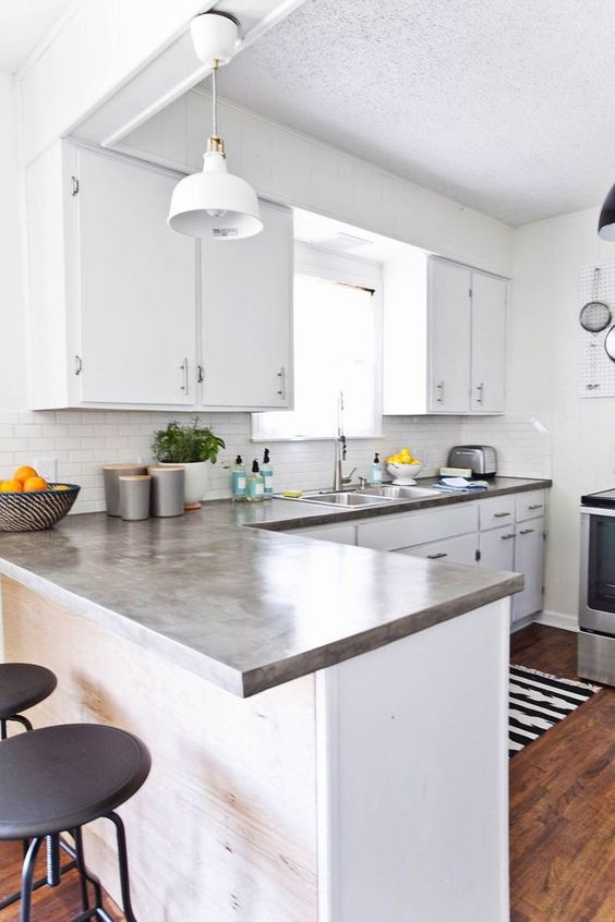 a modern white kitchen with cocnrete countertops, a white tile backsplash and black handles is chic