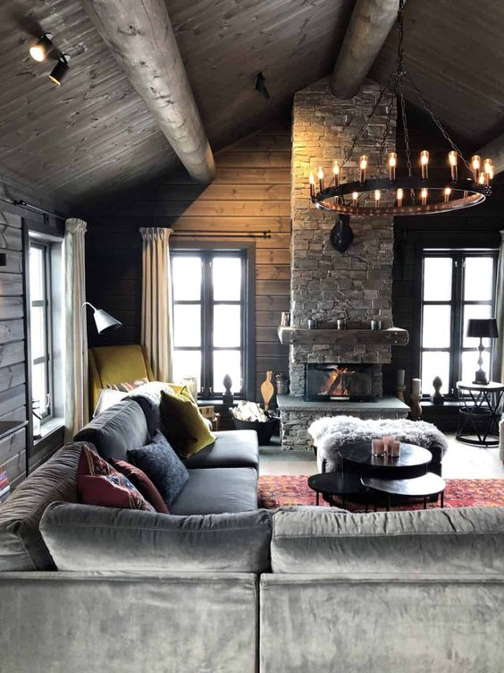 a moody chalet living room with wooden walls and a ceiling, a stone fireplace, a chandelier and comfortable and stylish furniture