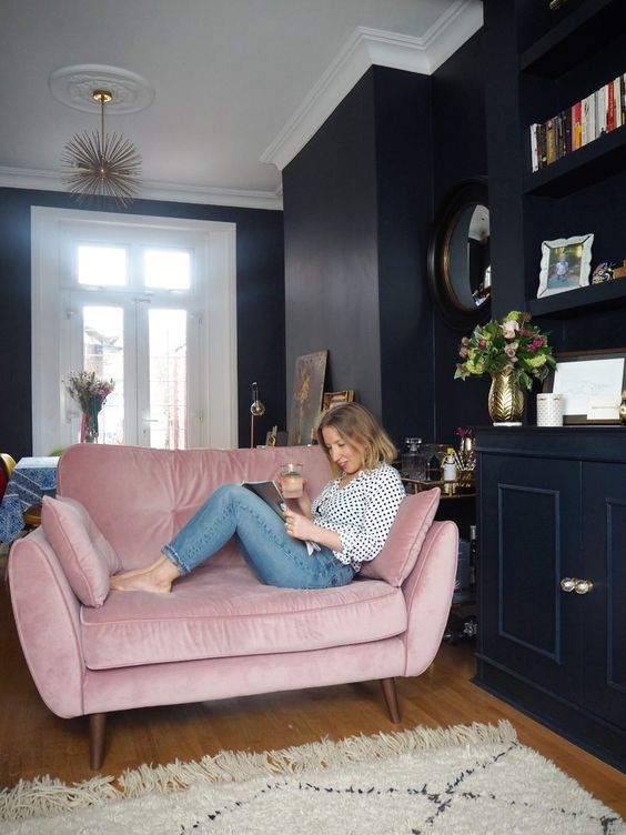 a moody navy room with chic modern decor and a pink loveseat with pillows that spruces up the space