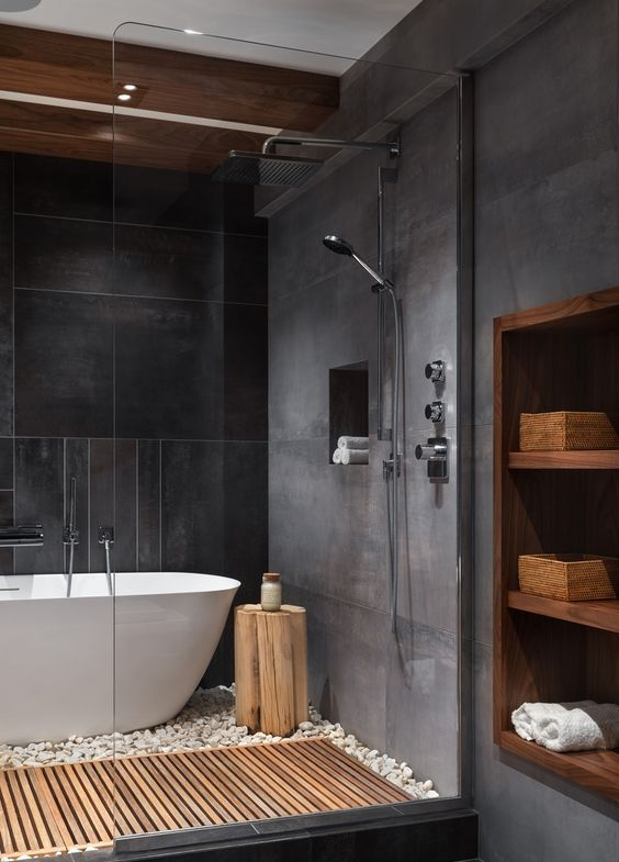 a moody spa-like bathroom with grey and black tiles, wooden beams and a mat and a wooden niche in the wall