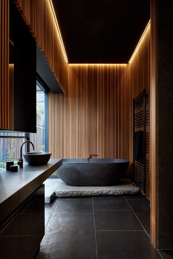 a moody spa-like bathroom with wooden slabs covering the walls, a stone tub platform and a stone vanity