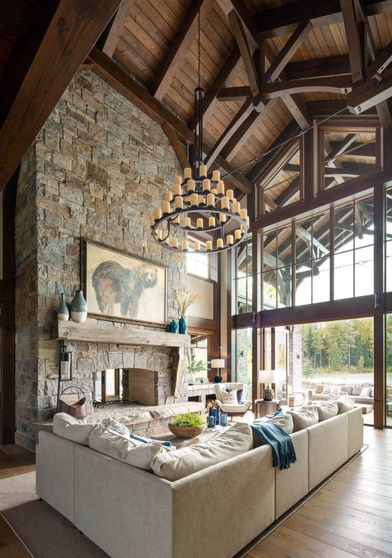 a mountain cabin living room with a wooden ceiling, a stone clad fireplace and stylish neutral furniture plus a statement chandelier
