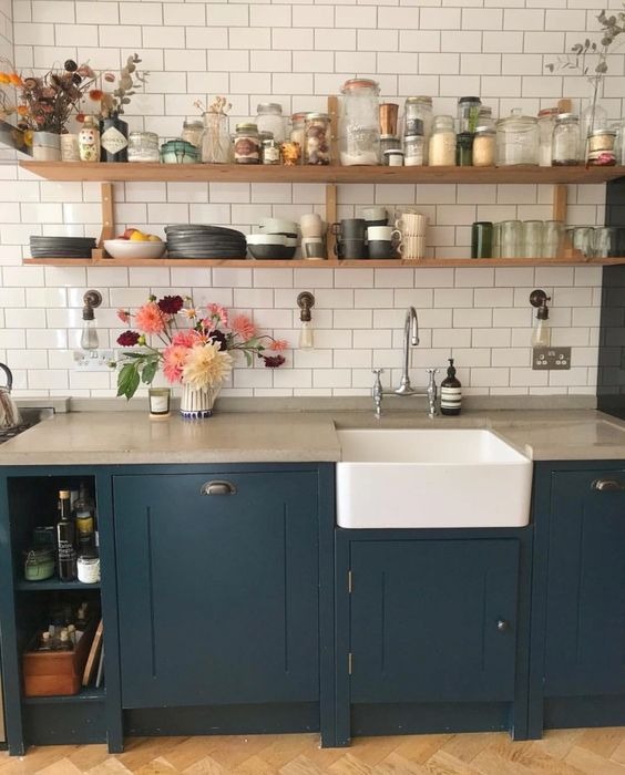 a navy farmhouse kitchen with concrete countertops, a white subway tile backsplash and open wooden shelves