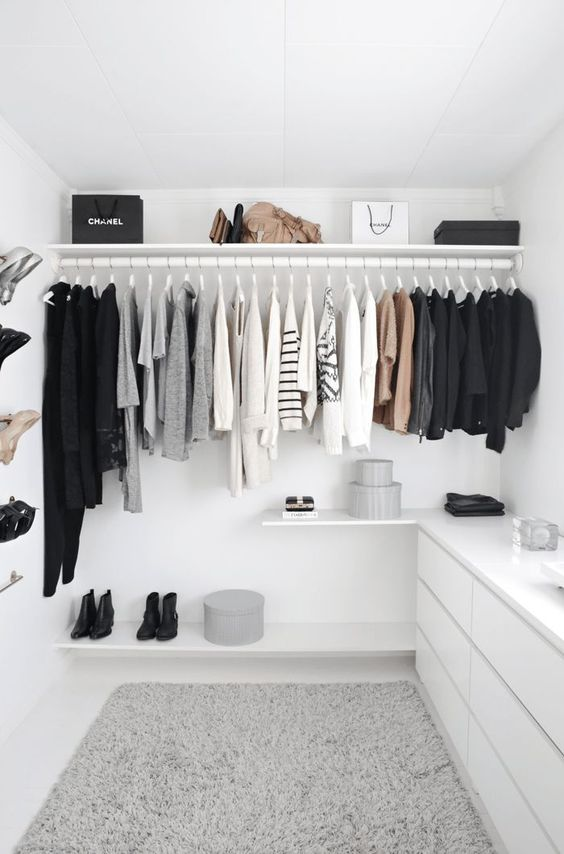 a neutral Scandinavian closet with a holder for clothes, a shelf for bags, a shelf with shoes, a sleek white dresser and boxes