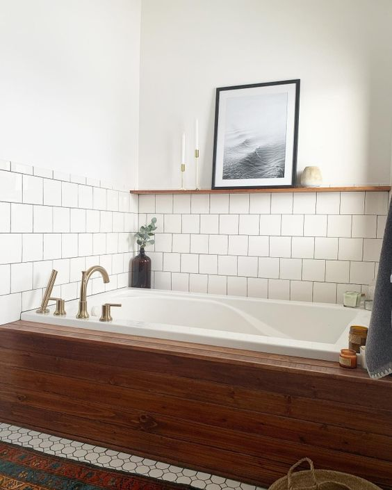 a neutral bathroom clad with two types of tiles and a bathtub accented with natural wood is super cozy and cool
