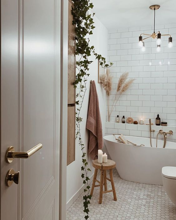 a neutral boho bathroom with various types of tiles, a climbing plant, a modern chandelier and pampas grass