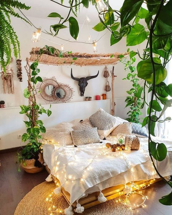 a neutral boho bedroom with lots of climbing plants, lights and boho pillows plus mirrors