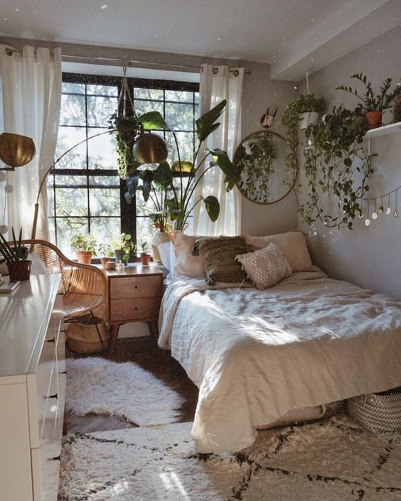 a neutral boho bedroom with wooden and rattan furniture, neutral bedding, potted greenery and climbing plants