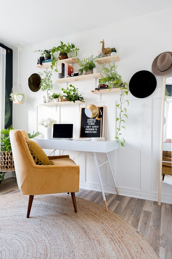 a neutral boho home office with a tiny desk, a yellow chair and open shelves with climbing plants in pots
