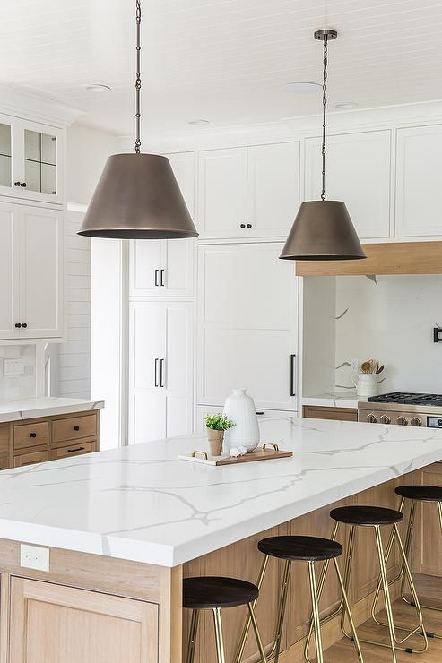 a neutral farmhouse kitchen with stained and white cabinets, white quartz countertops, a white marble tile backsplash and metal pendant lamps