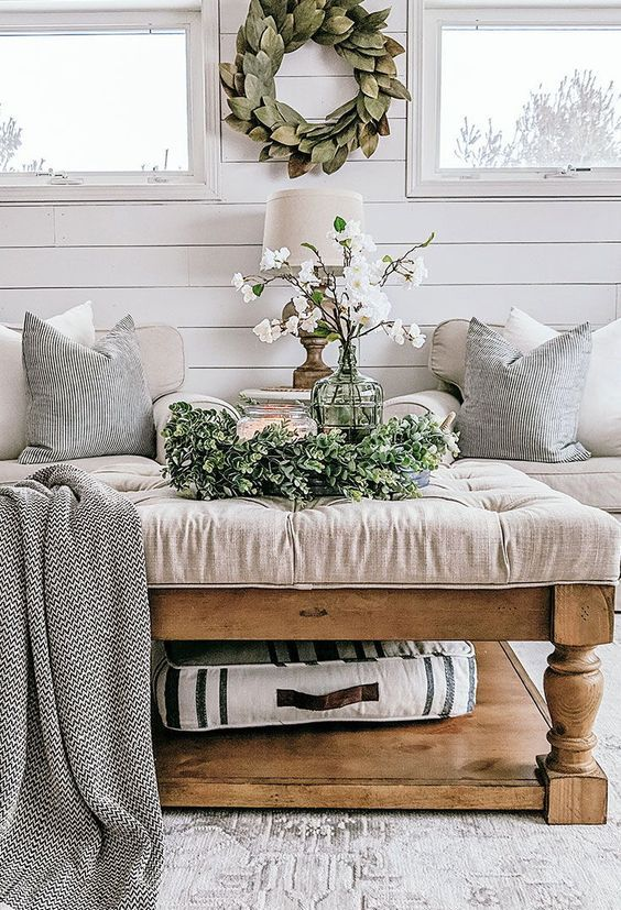 a neutral farmhouse living room with a greenery wreath, a leaf wreath and cherry blossom is a very fresh and welcoming space