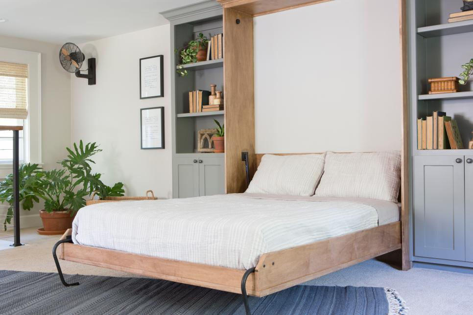 a neutral farmhouse space with a grey storage unit and a built-in Murphy bed plus potted plants and greenery
