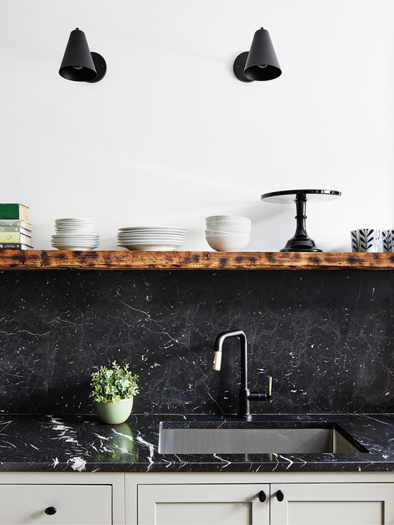 a neutral kitchen with black quartz countertops and a matching backsplash plus a floating shelf looks bold and chic