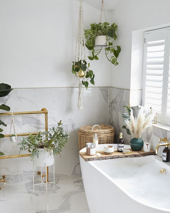a neutral refined bathroom with grey tile wall and floor, climbing plants, pampas grass and a modern tub