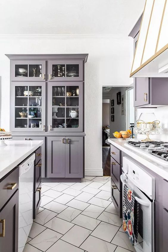 a pastel lavender kitchen with elegant vintage cabinetry, white stoen coutnertops, a cooker and a vintage hood with gold edges