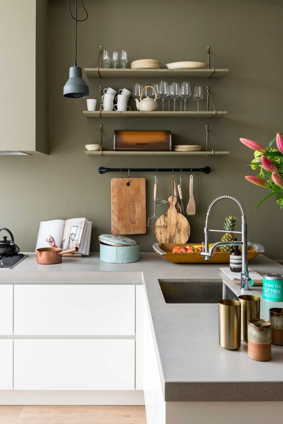 a peaceful Nordic kitchen with sleek white cabinets, concrete countertops, olive green walls and upper cabinets is a chic space