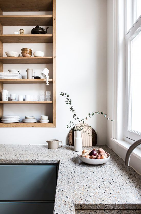 a peaceful blue kitchen with grey terrazzo coutnertops and a large built-in shelving unit plus greenery in a vase is beautiful