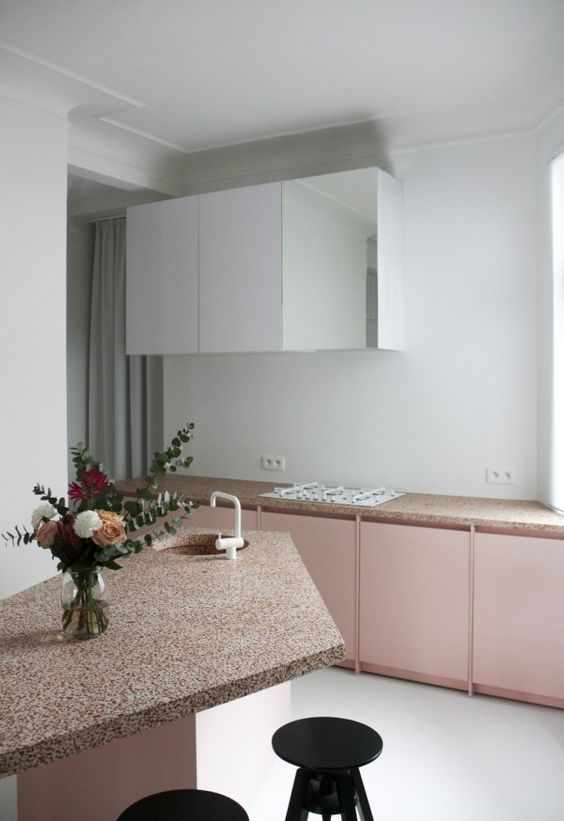 a pink and white kitchen with pretty pink terrazzo countertops and a geometric kitchen island plus black stools