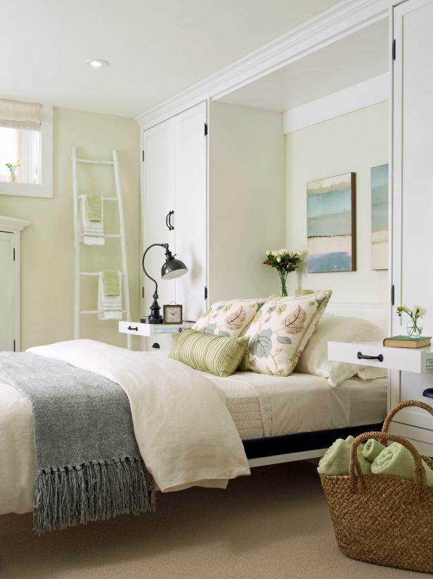 a pretty farmhouse bedroom in neutrals and pastels, with a storage unit and a Murphy bed plus vintage touches