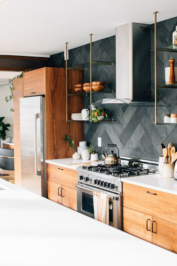 a pretty light stained kitchen with white coutnertops and a grey cement herringbone backsplash plus stainless steel appliances