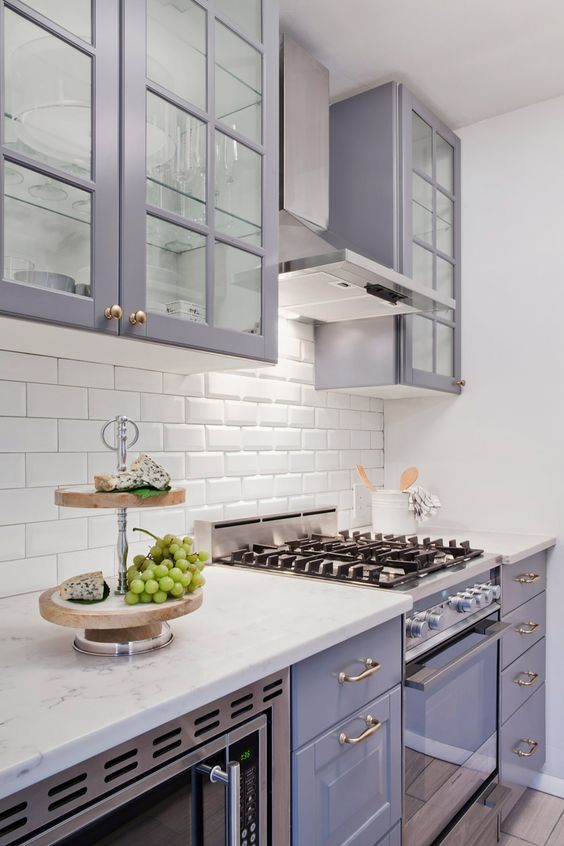 a pretty lilac kitchen with a white subway tile backsplash and white countertops plus brass and gold touches