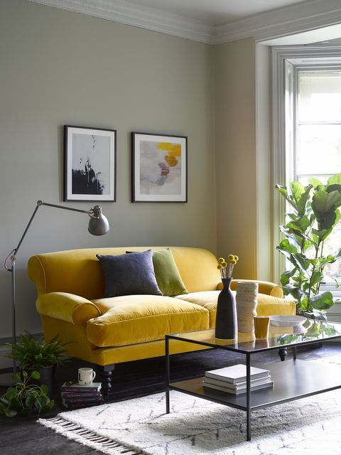 a pretty modern living roo, with green walls, a yellow loveseat, a black coffee table and potted plants