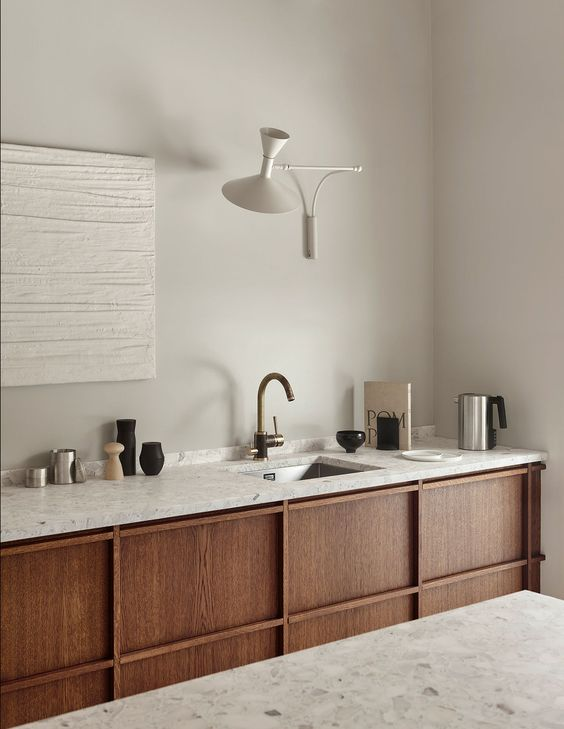a pretty rustic minimalist kitchen with stained cabinetry and grey terrazzo countertops is a lovely and welcoming space