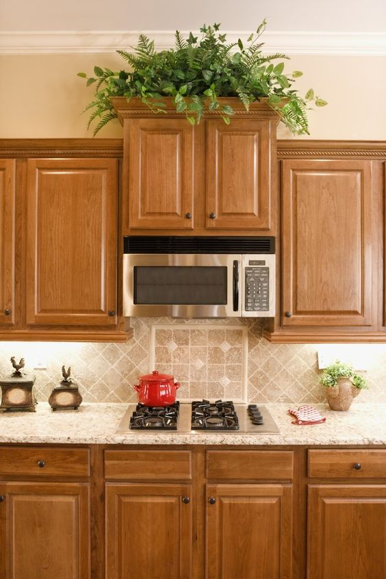 a pretty stained kitchen with a grey tile backsplash and grey granite countertops plus built-in lights is elegant and cool